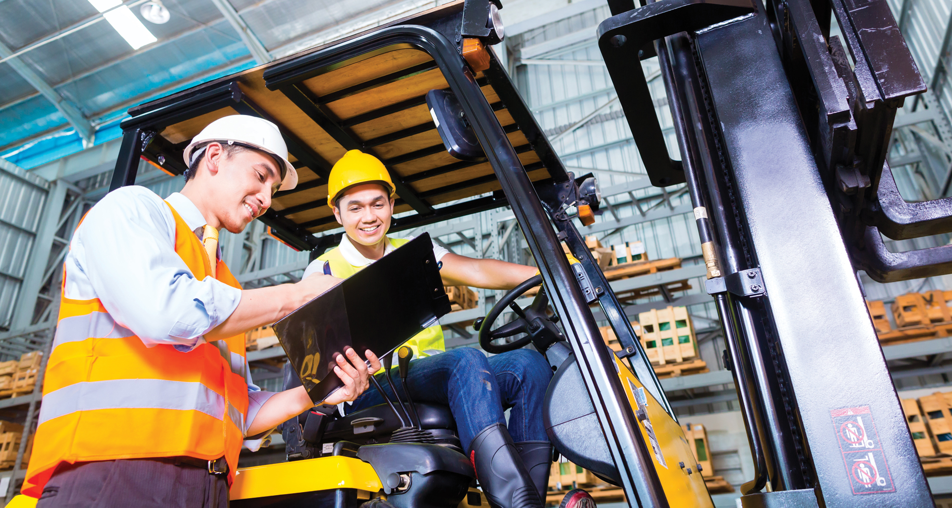Blue collar workers with safety vests discussing documents on a clipboard.