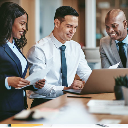 Young, diverse businessmen and women discuss information in front of a computer screen.