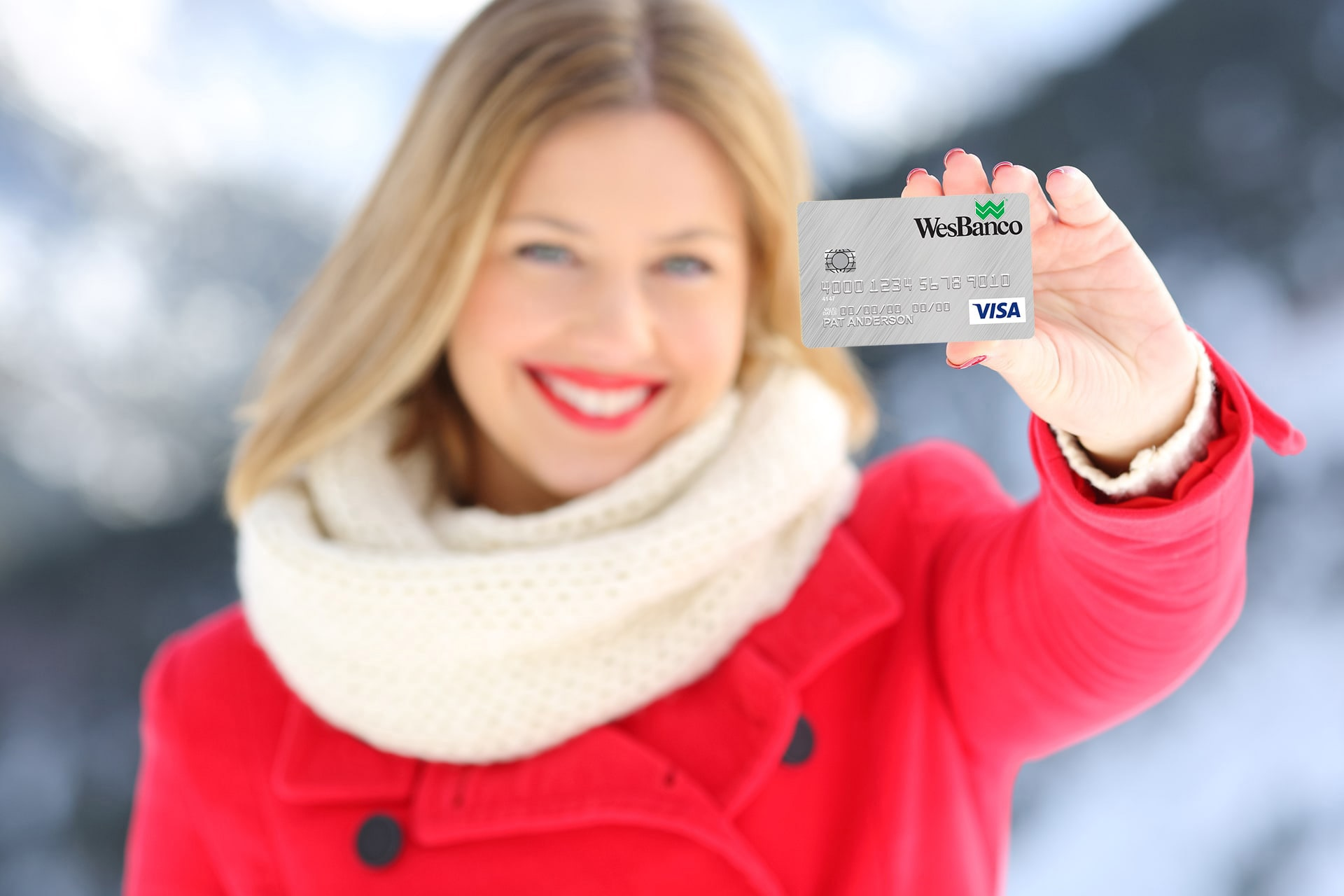 Smiling blonde woman in a red winter coat with white trim excitedly holds up a Personal WesBanco Credit Card