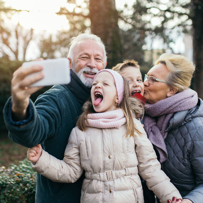 Grandparents taking cell phone pic with grandchildren
