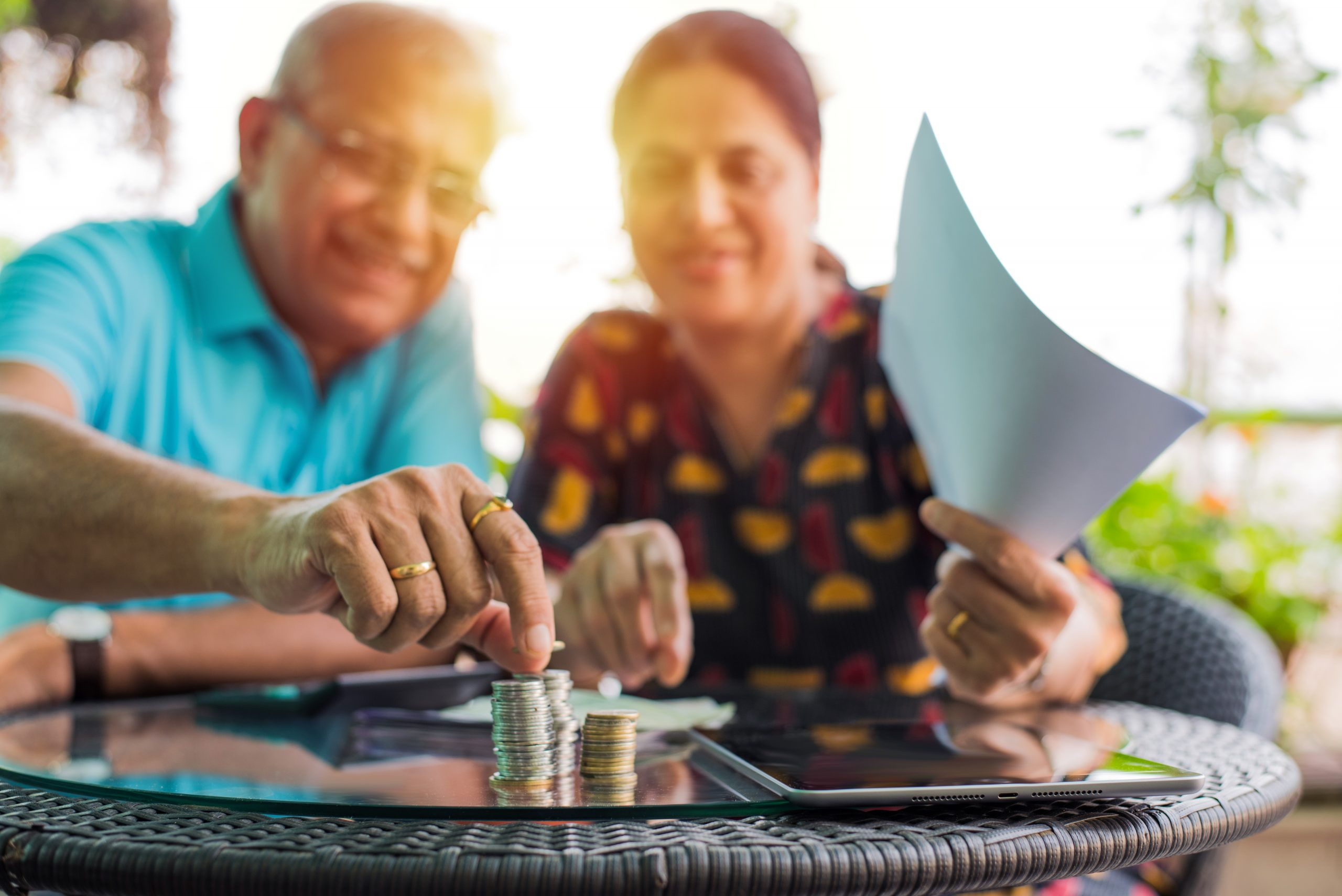 Elderly East Asian couple counting coins