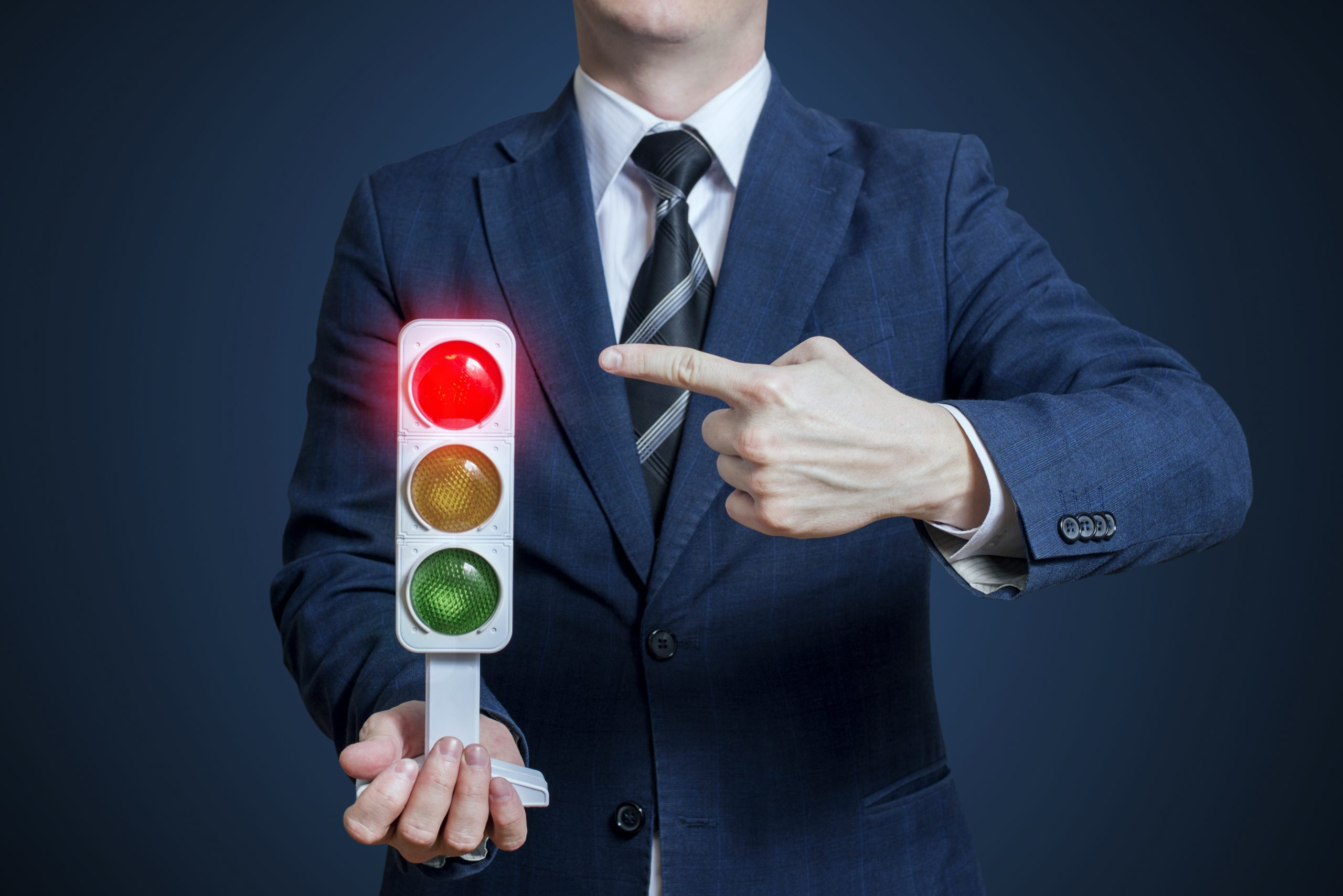 Businessman holding a traffic light with red light on. Business concept