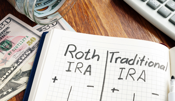 Notebook sitting on top of fifty dollar bills, the words Roth IRA and Traditional IRA written in marker