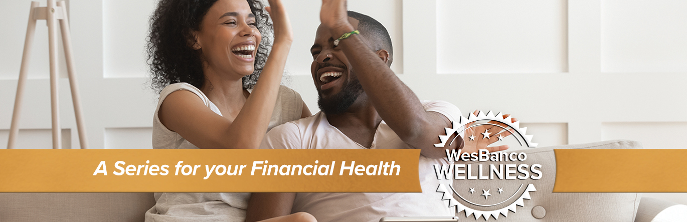 A young couple cheerfully high-five each other while sitting on a couch. The words A Series for your Financial Health in orange banner in the foreground.