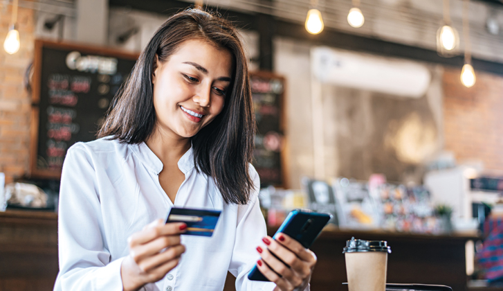 Young woman at a cofee shop holds her phone in one hand and her financial card in another.