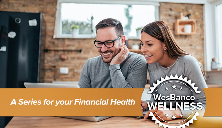 Young couple smiles down at a computer screen. In the foreground, an orange banner with the words A Series for Your Financial Health