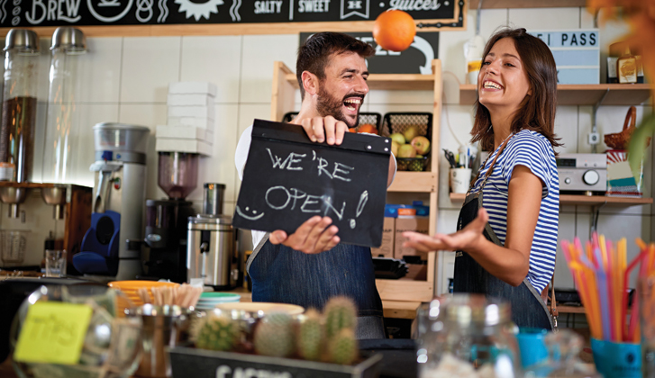 Business-owning couple with excited smiles holding a sign that says We're Open