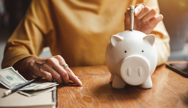 A woman sits at a wooden table with dillar bills near her left hand, depositing one into a white piggy bank.