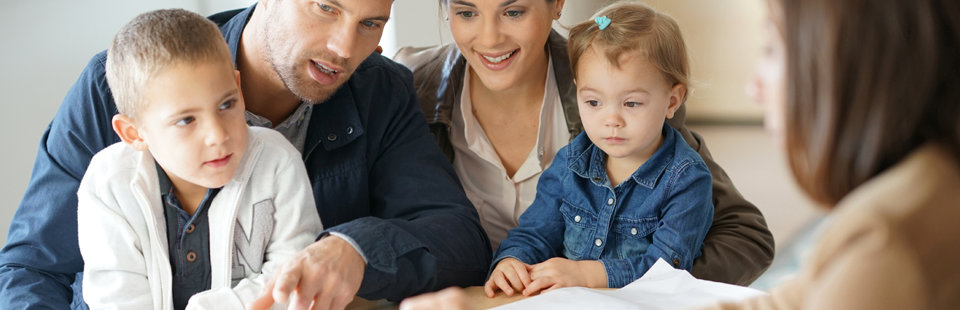 Young couple with two children on their laps reviews documents