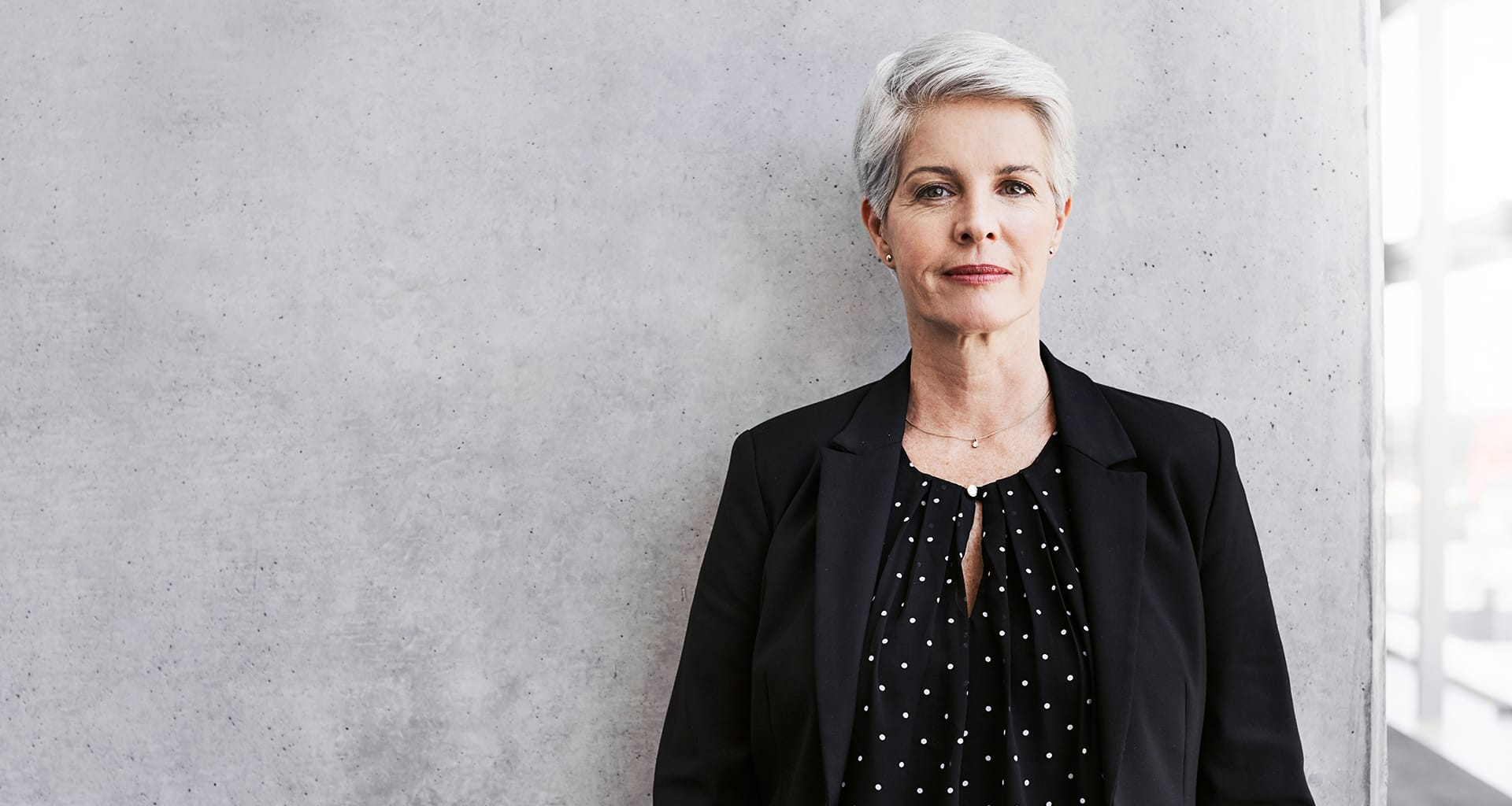 Slender woman with grey hair standing next to a window.