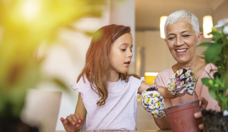 Grandmother and child potting flowers