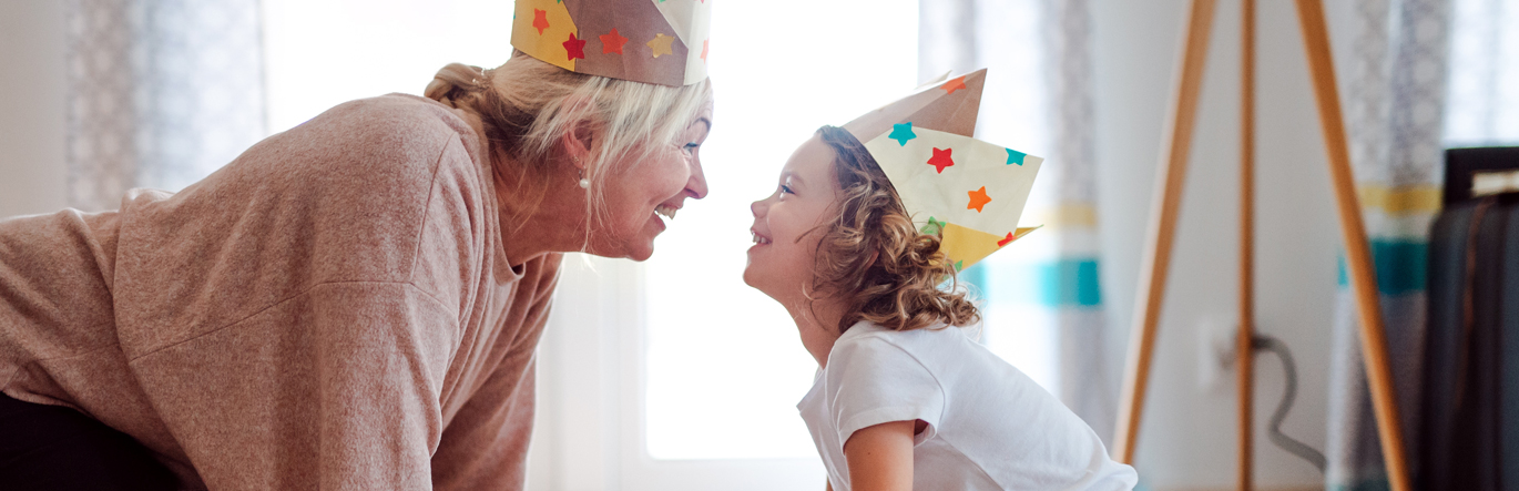 Grandmother with grandchild wearing party hats on