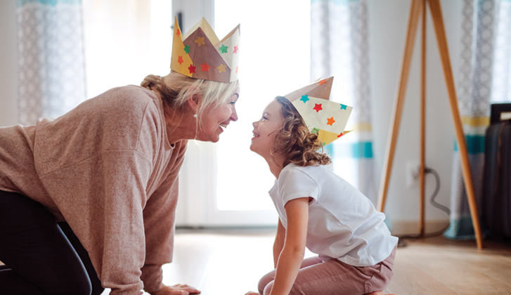 Grandmother with grandchild wearing party hats