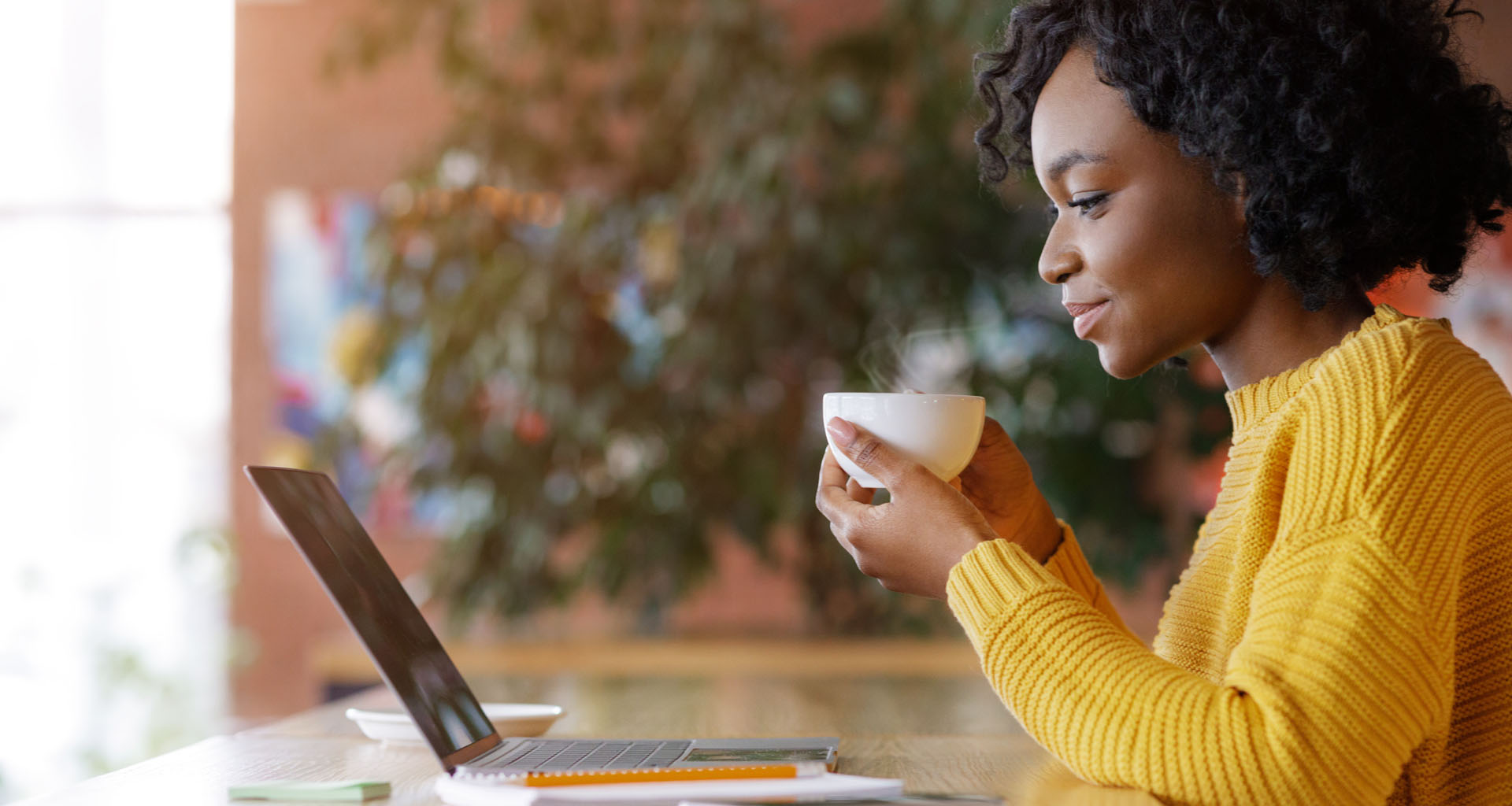 African American woman working from laptop while drinking from mug