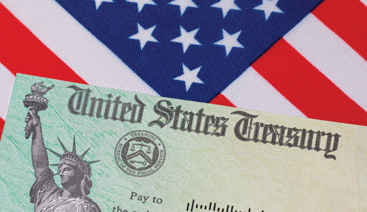 Green US Treasury check with the Statue of Liberty on it on top of an American flag.
