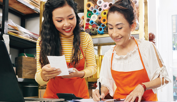 Asian mother and daughter business owners doing their books
