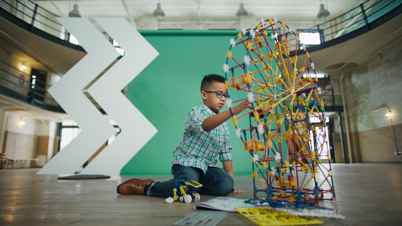 Young child works on building a puzzle in front of a green structure with the WesBanco Mark