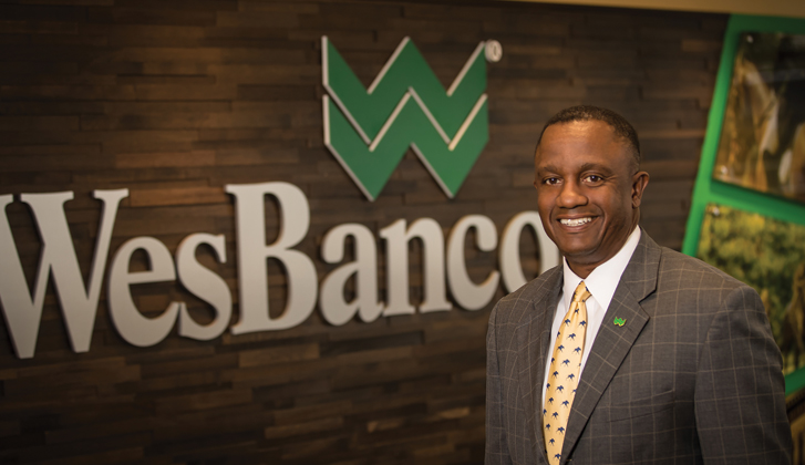 Abdul Muhammad standing in front of WesBanco logo