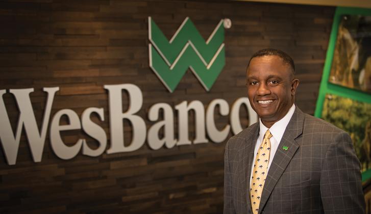 Abdul Muhammad standing in front of WesBanco logo
