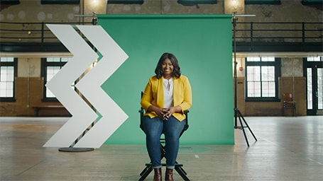 Woman in yellow jacket sits in front of a green structure with the WesBanco mark