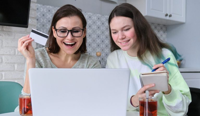 Mother and daughter using laptop credit card and doing online shopping