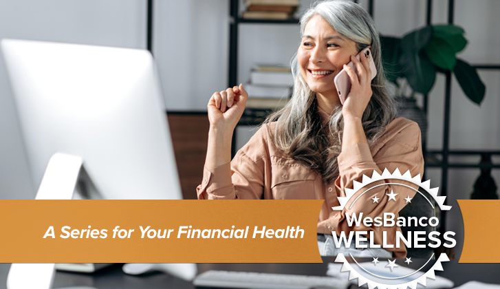 Older asian woman on cellphone at desk.